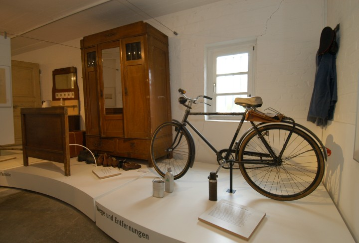 view into the exhibition, with an old bike and furniture