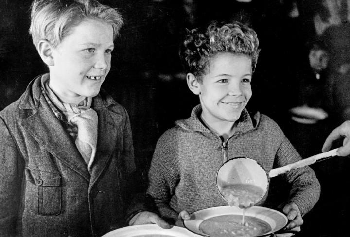 Schwarz-Weiss Foto zeigt zwei Jungen die eine Teller Suppe in einer Großküche bekommen