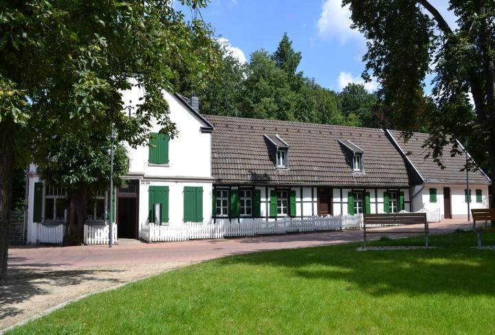 Foto zeigt die Außenansicht des weißes Hauses mit grauem Dach und einer grünen Wiese davor