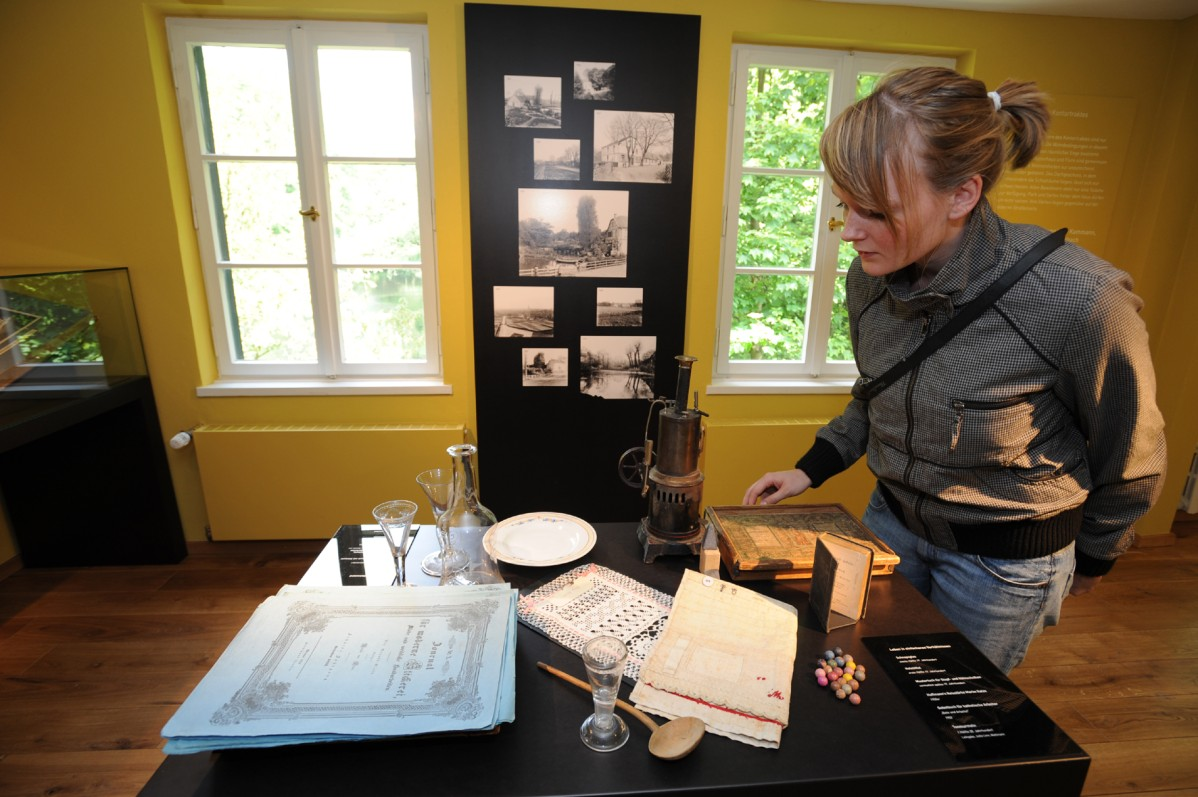 Woman looks at objects in the exhibition in the St. Antony Hütte