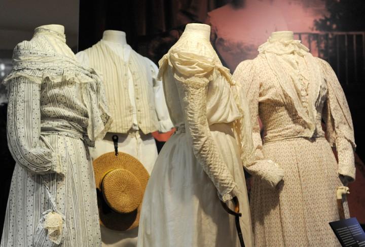 Vier helle Damenkleider an Figurinen