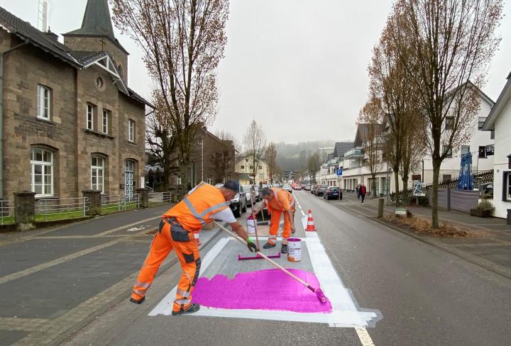 Straßenarbeiter streichen ein Stück Straße in Pink